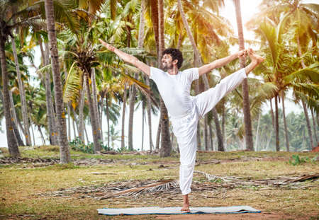 Yoga by happy Indian man in white trousers near palm trees in Kerala, India photo