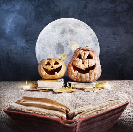 Halloween pumpkins reading old book at full moon and dark sky background photo