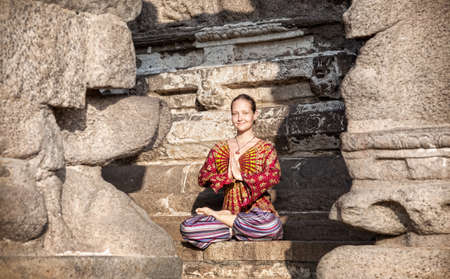 mamallapuram: Woman in lotus pose with hands in Namaste gesture sitting near Shore temple, Mamallapuram, Tamil Nadu, India Stock Photo