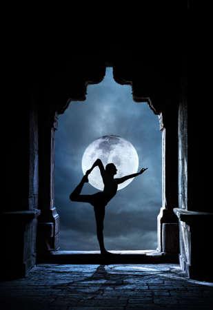 満月の夜の空の背景に古いお寺でヨガをやっている人シルエット