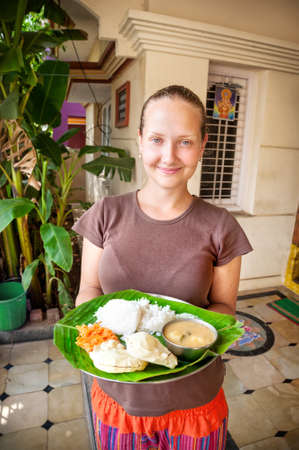 Woman holding Indian traditional thali on banana leaf photo