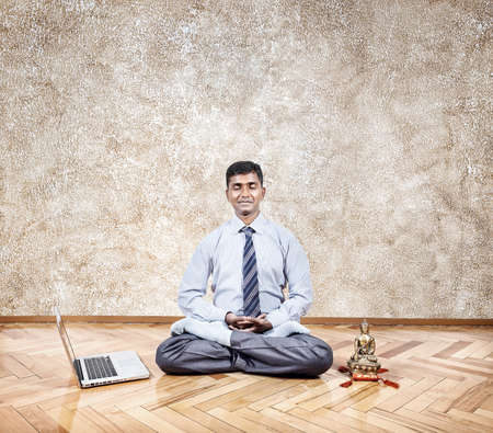 Happy Indian businessman doing meditation nearby laptop and Buddha statue in the office  photo