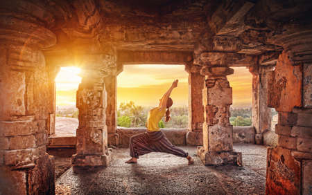 Woman doing yoga in ruined ancient temple with columns at sunset in Hampi, Karnataka, India