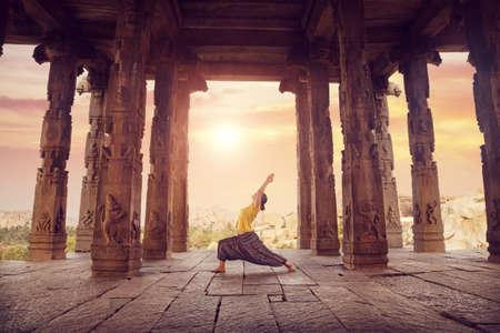 karnataka: Mujer que hace yoga en el antiguo templo en ruinas con columnas, Hampi, Karnataka, India
