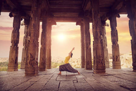 Woman doing yoga in ruined ancient temple with columns, Hampi, Karnataka, India Imagens - 23666422