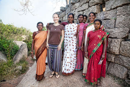 mamallapuram: Mamallapuram, INDIA - January 24  Group photo of Caucasian woman with local Indian women in traditional Indian colorful saris in Mamallapuram cave complex on January 24, 2013  Local Indians very like to take pictures with foreign white tourists