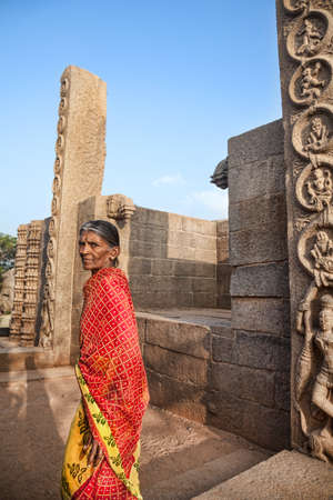 mamallapuram: Mamallapuram, INDIA - January 24  Old Indian woman in red sari walking in Mamallapuram Temple on January 24, 2013