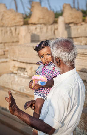 mamallapuram: Mamallapuram, INDIA - January 24  Old Indian man with little girl in Mamallapuram Shore Temple on January 24, 2013