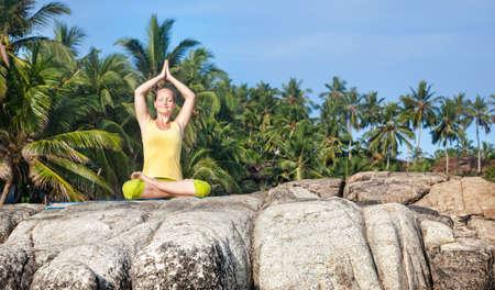 paz interior: Mujer que hace yoga loto plantean en la piedra en el cielo azul y el fondo tropical en Kovalam, Kerala, India Foto de archivo