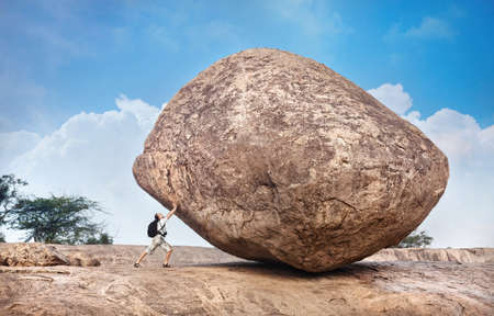 Man met rugzak duwen een enorme steen in Mamallapuram grottencomplex, Tamil Nadu, India