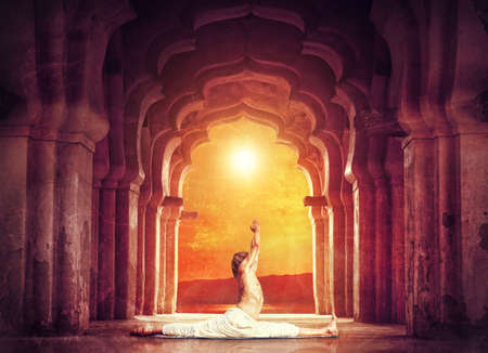 ancient yoga: Man doing yoga in old temple at orange sunset sky background