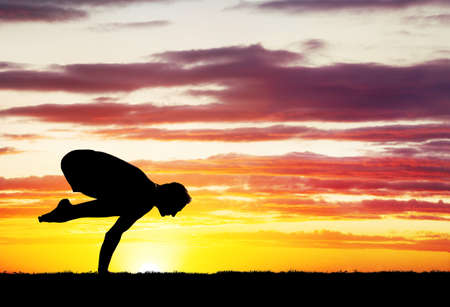 siluet: Man doing Yoga on the grass at sunset sky Stock Photo