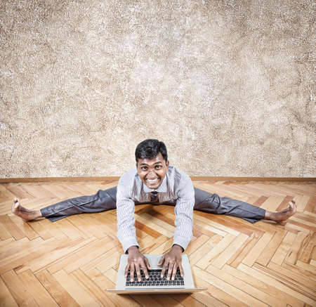 Happy Indian businessman doing yoga with laptop in the office  photo