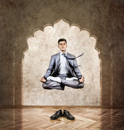 Indian businessman doing meditation in the air in lotus pose at the office with arch on the wall photo