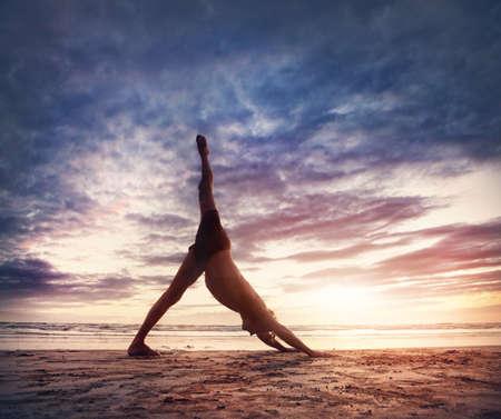 yoga sunset: Man doing Yoga on the beach near the ocean in India