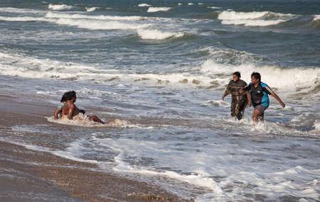 mamallapuram: Mamallapuram, Tamil Nadu, INDIA - January 23  Indian people swimming in the ocean on Mamallapuram beach on January 23, 2013