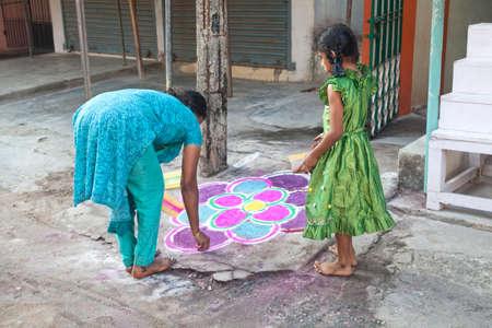 mamallapuram: Mamallapuram, Tamil Nadu, INDIA - January 25  Indian mother and daughter painting mandala in front of their home on the street in Mamallapuram on January 25, 2013  Editorial