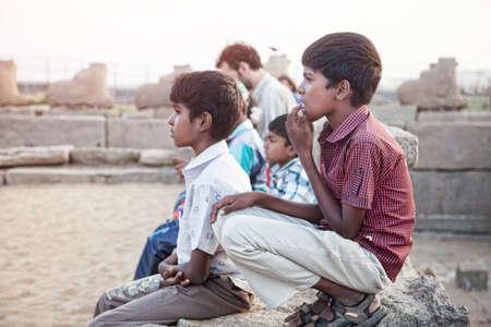 mamallapuram: Mamallapuram, Tamil Nadu, INDIA - January 24  Indian school boys sitting on the stones near Shore Temple on January 24, 2013