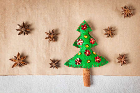 Handmade decorated Christmas tree from felt and star anise around on brown paper  photo