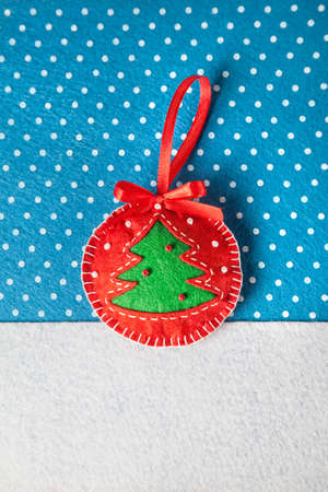 Handmade toy with Christmas tree from felt on blue with snowflakes photo