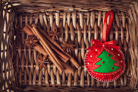 Christmas handmade red toy with tree from felt, cinnamon and star anise in brown twiggen basket photo