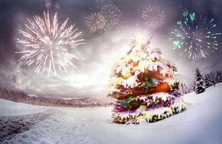 snow scene: Christmas tree with lightings in the forest at dramatic sky with fireworks