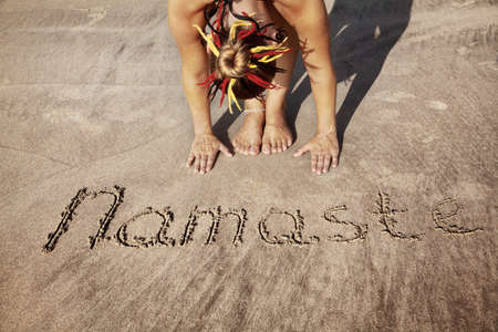 india people: Woman doing yoga on the beach near Namaste handwriting in Goa, India
