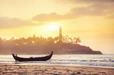 Indian fisherman in silhouette with fishing boat on the beach in the morning at lighthouse background in Kovalam, Kerala, India   photo