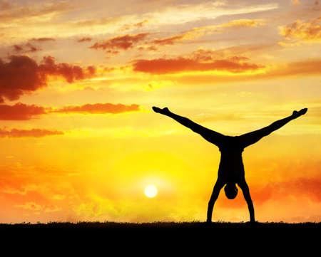 siluet: Man doing Yoga handstand on the grass at sunset sky