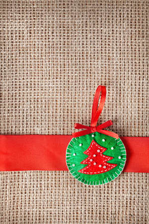 Christmas handmade toy with tree from felt on sackcloth background photo
