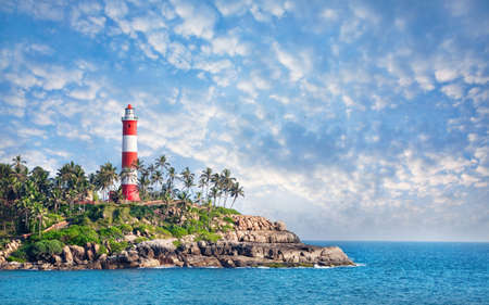 Lighthouse on the rocks near the ocean at blue sky with clouds in Kovalam, Kerala, India