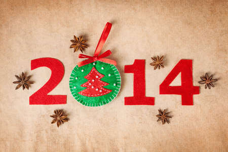 2014 new year with christmas toy from felt and star anise around on paper background photo