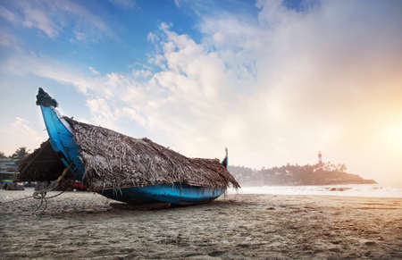 kovalam: Fishing boat with palm tree leaves on the beach in the morning at lighthouse in Kovalam, Kerala, India   Stock Photo