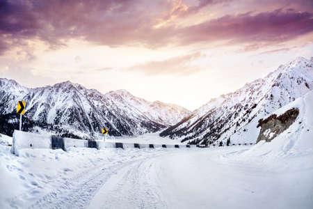 Sneeuw weg in de bergen in de buurt van Big Almaty Lake bij zonsopgang in Kazachstan Stockfoto