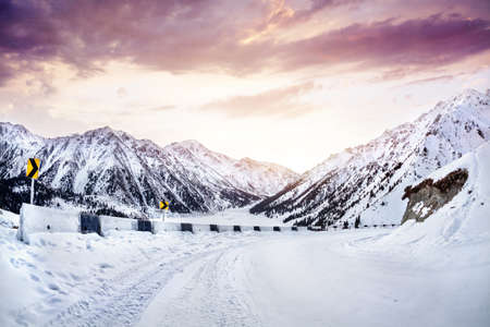 mountain road: Snow road in the mountains near Big Almaty Lake at sunrise in Kazakhstan Stock Photo
