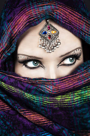 Portrait of beautiful woman wrapped in scarf with Indian tikka