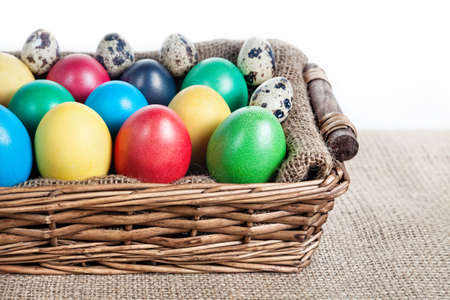 Easter painted and quail eggs in the basket on sackcloth on white background photo