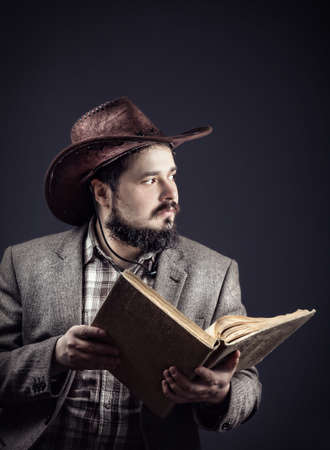 old cowboy: Cowboy with moustache and beard holding old book at dark background Stock Photo
