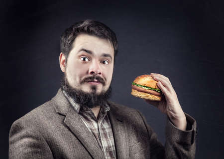 Man in jacket with beard holding hamburger at dark background photo