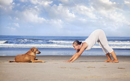 downward: Woman in white costume doing Yoga and looking at the dog on the beach near the ocean in India