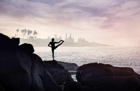 kovalam: Man doing Yoga one leg balance pose on the rocks at ocean and mosque background
