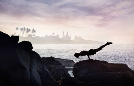 Man doing Yoga handstand on the rocks at ocean and mosque background Stock Photo