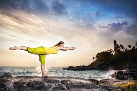 indian yoga: Woman doing yoga on the stone nearby ocean at lighthouse background in Kovalam, Kerala, India Stock Photo