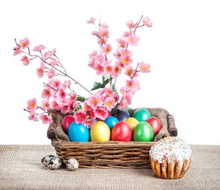 Easter painted eggs in the basket with pink flowers and easter cake on white background photo