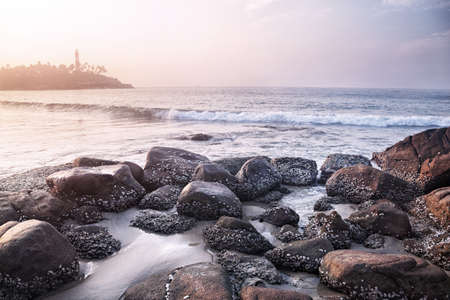 kovalam: View to Lighthouse on the hill from the stones near the ocean in Kovalam, Kerala, India