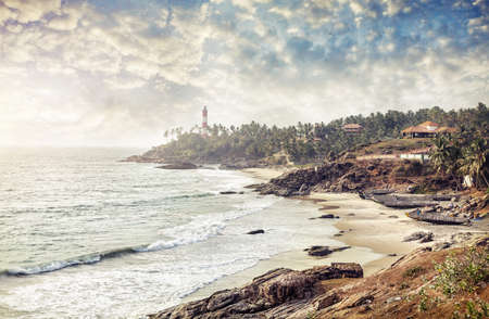 kovalam: Lighthouse on the hill near the ocean at blue sky with clouds in Kovalam, Kerala, India   Stock Photo