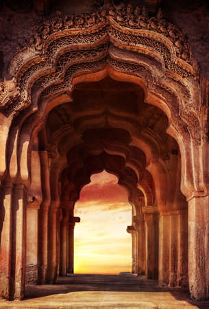 インドの日没での古代寺院の古い台無しにされたアーチ