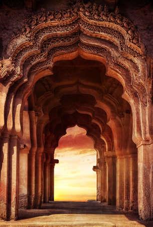 Oude geruïneerde boog in oude tempel bij zonsondergang in India