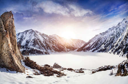 snow covered mountain: Big Almaty Lake in snowy mountains at sunrise in Kazakhstan