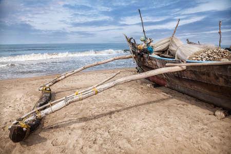 india fisherman: Fisherman boat with fishing nets on the Gokarna beach near the ocean in Karnataka, India